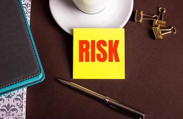 コーヒーカップと日記の近くの茶色の背景に黄色い紙に書かれたリスクという言葉