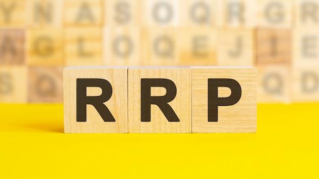 Слово rrp написано на деревянных кубиках на ярко-желтой поверхности. на заднем плане ряды кубиков с разными буквами. концепция бизнеса и финансов. rrp - рекомендованная розничная цена