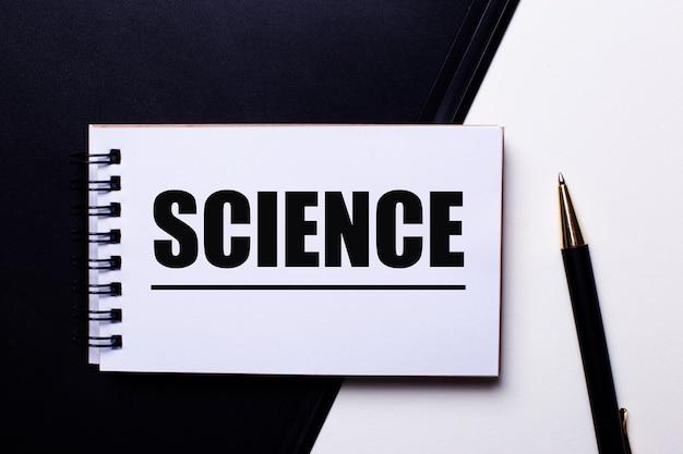 펜 근처의 흑백 테이블에 빨간색으로 쓰여진 과학이라는 단어