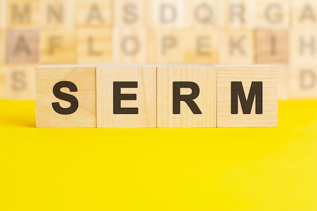 Слово serm написано на деревянных кубиках на ярко-желтой поверхности. на заднем плане ряды кубиков с разными буквами. концепция бизнеса и финансов