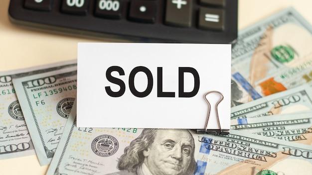 Слово продано написано на белой карточке. карточка на фоне 100 долларовых купюр и калькулятора.