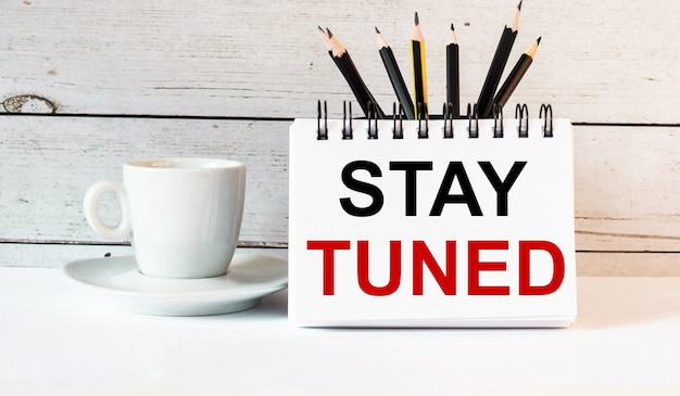 Слово stay tuned написано в белом блокноте возле белой чашки кофе на светлой поверхности.