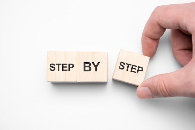 木製の立方体のステップバイステップの言葉。ビジネスキャリアの達成または進歩。