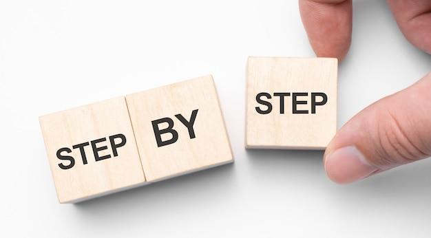 木製の立方体のステップバイステップという言葉。ビジネスキャリアの達成または進歩。