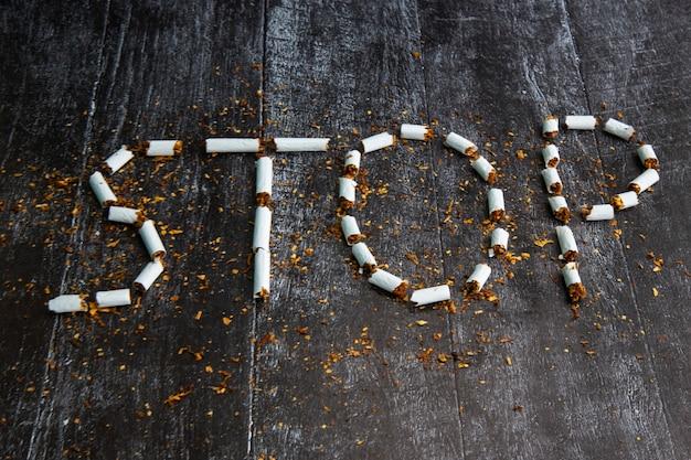Слово стоп написано при помощи сигарет на темном фоне. концепция: вред курения, бросить курить