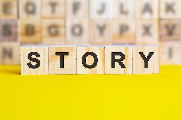 物語という言葉は、明るい黄色の表面にある木製の立方体に書かれています。背景には、異なる文字の立方体の行があります。ビジネスと金融の概念