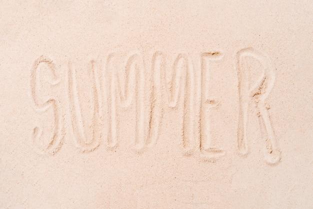 여름 휴가의 모래 해변 배경 개념에 손가락으로 쓰여진 단어 여름은 공간을 복사