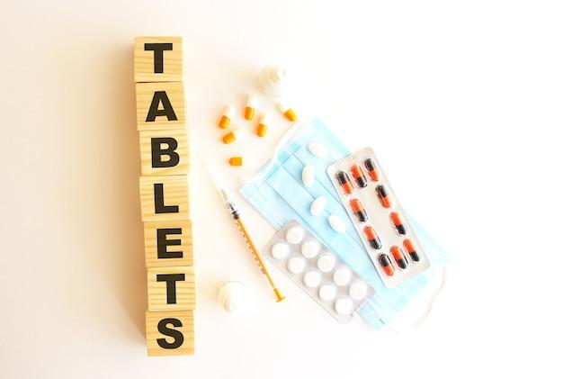 タブレットという言葉は、白い背景に医薬品と医療用マスクが付いた木製の立方体でできています。