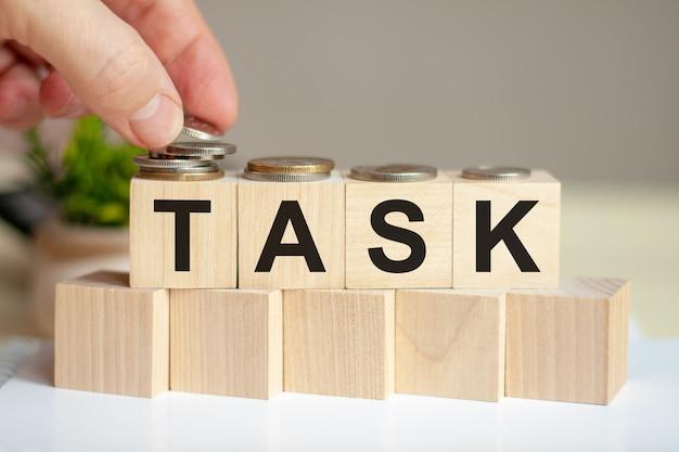 男の手で木製の立方体に書かれた単語タスクは、背景のビジネスと金融の概念の立方体の緑の鉢植えの植物の表面にコインを置きます