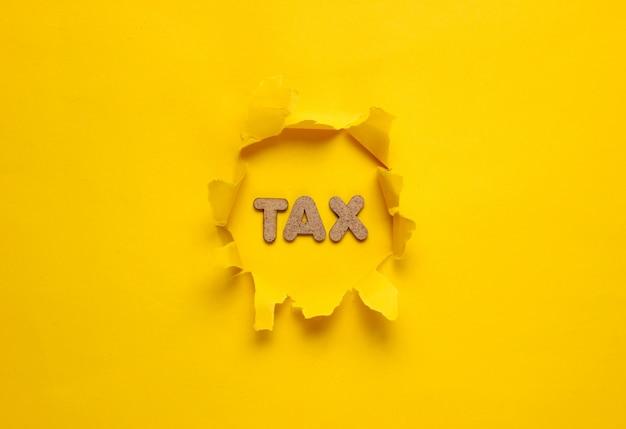 黄色の表面の破れた穴に税金という言葉。