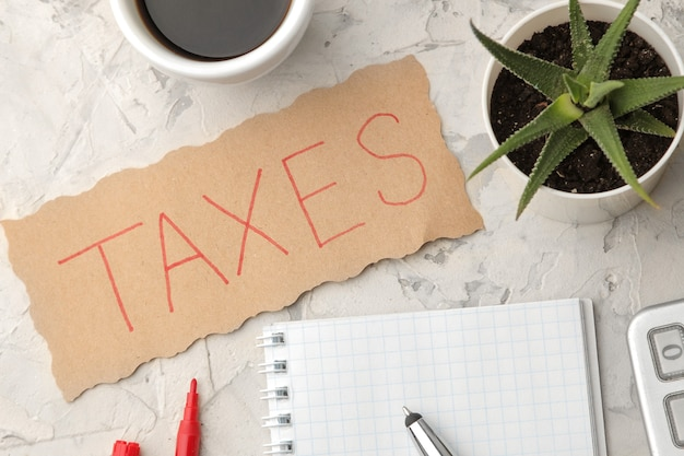 明るいコンクリートの背景にコーヒーとペンが付いたノートの紙に税金という言葉があります。上からの眺め