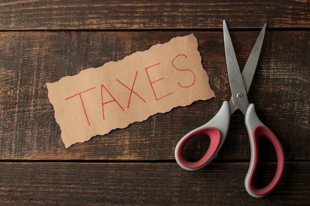 茶色の木製の背景にハサミで税金という言葉。上からの眺め