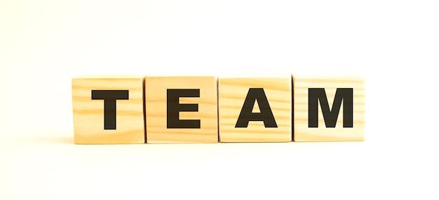 팀이라는 단어. 흰색 배경에 고립 된 편지와 함께 나무 큐브. 개념적 이미지.