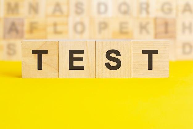Слово тест написано на деревянных кубиках на ярко-желтой поверхности. на заднем плане ряды кубиков с разными буквами. концепция бизнеса и финансов