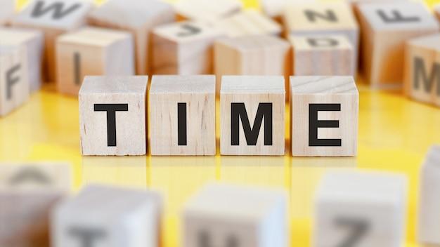나무 큐브 구조에 time이라는 단어가 쓰여 있습니다. 밝은 배경에 블록입니다. 금융 개념입니다. 선택적 초점.