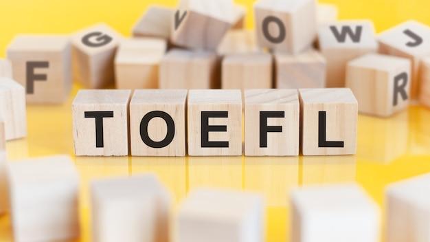 単語toeflは、明るい背景の木製の立方体構造ブロックに書かれています金融概念選択的焦点toefl外国語としての英語のテストの略