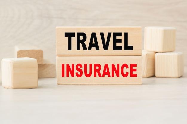 Слово travel insurance написано на деревянной конструкции из кубиков.