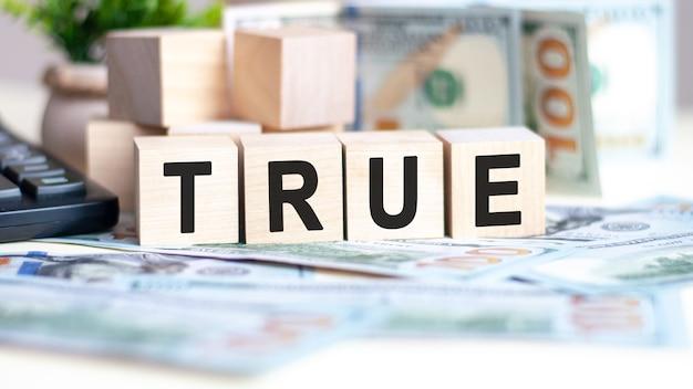 Слово true на деревянных кубиках, банкнотах и калькуляторе на поверхности