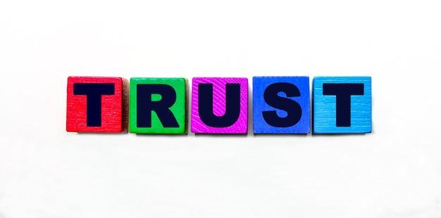 Слово доверие написано на разноцветных кубиках на светлом фоне.