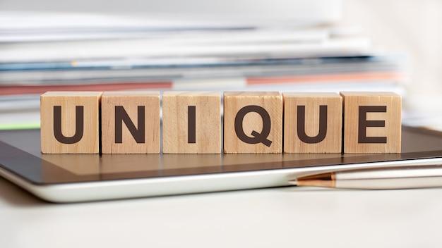 고유 한 단어는 태블릿에 서있는 나무 큐브에 기록됩니다. 비즈니스, 교육, 금융, 마케팅 개념에 사용할 수 있습니다.