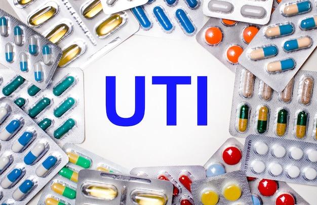 Слово «имп» написано на светлом фоне в окружении разноцветных упаковок с таблетками. медицинская концепция