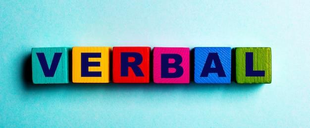 Слово verbal написано на разноцветных ярких деревянных кубиках на голубой поверхности.