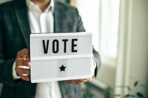 남자의 손에 있는 라이트박스에 vote라는 단어가 쓰여 있습니다. 선거 개념입니다.