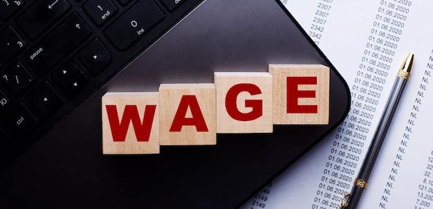 Слово wage написано на деревянных кубиках на клавиатуре рядом с ручкой.