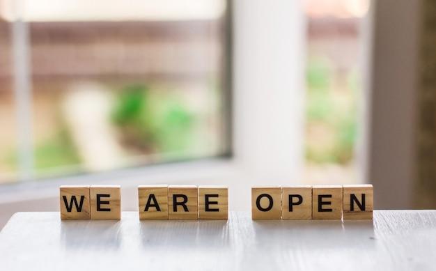 우리는 열린 문을 배경으로 나무 큐브로 만든 단어입니다. 검역 종료 코로나 바이러스 발생 및 사람들의 폐쇄 후 손님을 맞이하는 지역 상점