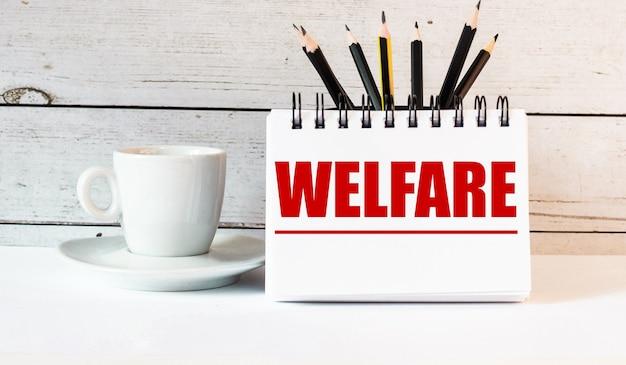 Слово welfare написано в белом блокноте возле белой чашки кофе на светлой стене.