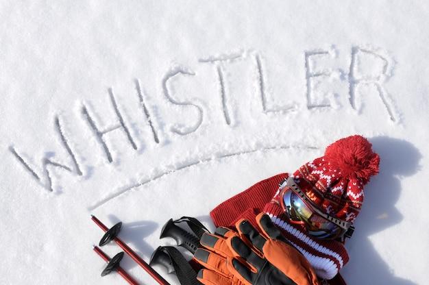 Слово уистлер написано на снегу с лыжными палками, защитными очками и шляпами