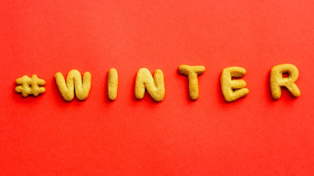 赤い背景のクッキーから冬という言葉。上からの眺め、テキストの場所