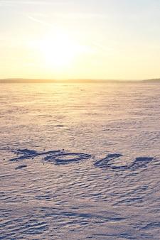 雪の中で書かれた「あなた」という言葉。夕日の背景。