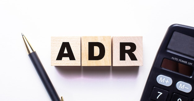 Adr裁判外紛争解決という言葉は、明るい背景のペンと電卓の間の木製の立方体に書かれています