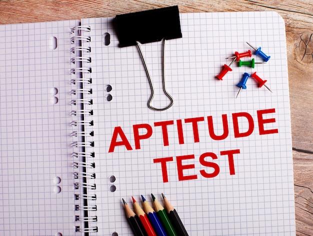 Aptitude testという言葉は、木製の表面にある色鉛筆とボタンの近くのノートに書かれています