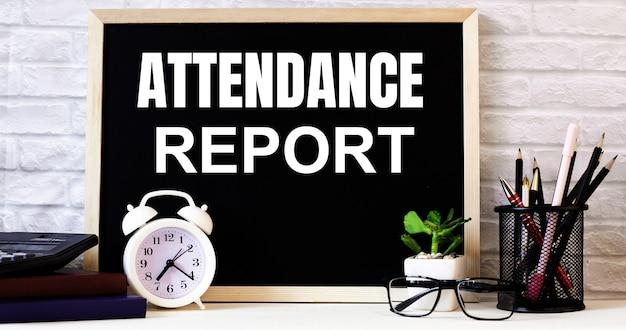 Attendance reportという言葉は、白い目覚まし時計、グラス、鉢植え、スタンドの鉛筆の横にある黒板に書かれています。