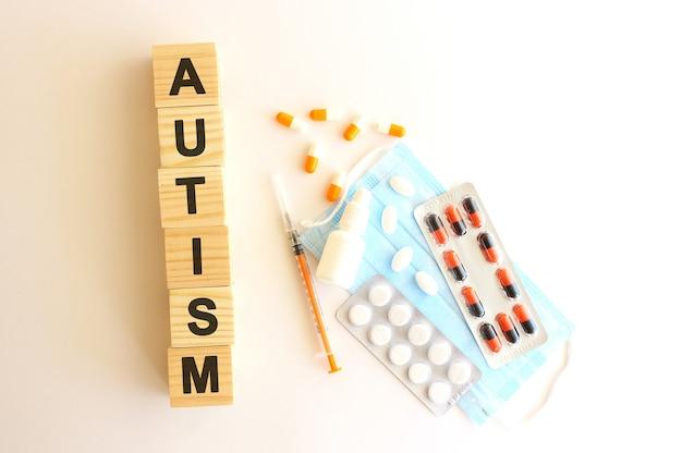 Autismという言葉は、医薬品と医療用マスクが付いた木製の立方体でできています。医療コンセプト。