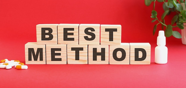 Bestmethodという言葉は赤い背景の木製の立方体でできています。