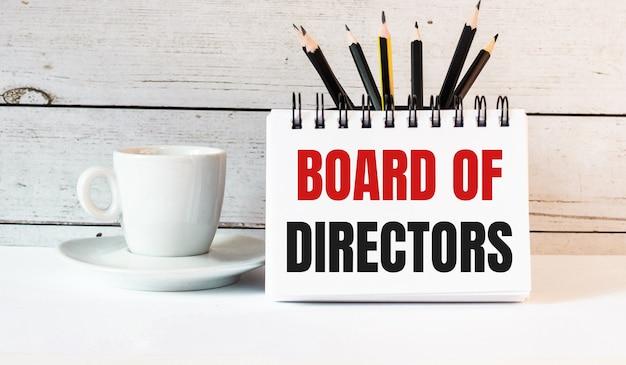 Слова совет директоров написаны в белом блокноте возле белой чашки кофе на светлом фоне.