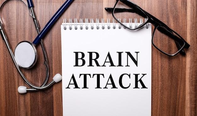 뇌 공격이라는 단어는 청진기와 검은 색 안경테 근처의 나무 배경에 흰 종이에 쓰여 있습니다.