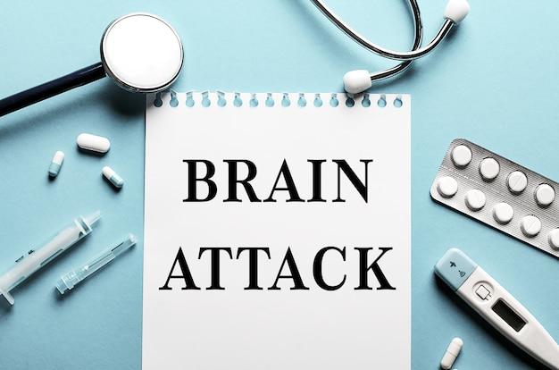 청진 기, 주사기, 전자 온도계 및 알 약 근처 파란색 표면에 흰색 메모장에 쓰여진 단어 뇌 공격. 의료 개념.