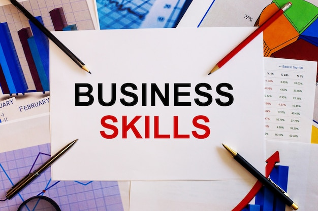 비즈니스 기술이라는 단어는 컬러 그래프, 펜 및 연필 근처의 흰색 배경에 기록되어 있습니다.
