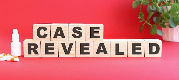 Case revealedという言葉は、赤い背景に医薬品が入った木製の立方体でできています。
