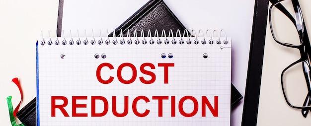 コスト削減という言葉は、黒いフレームのメガネの横にある白いノートに赤で書かれています