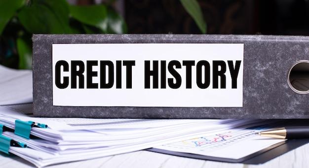 Слова кредитная история написаны на серой папке с файлами рядом с документами.