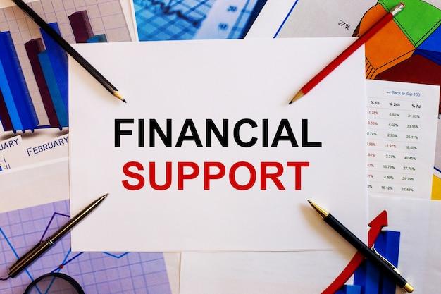Слова «финансовая поддержка» написаны на белой поверхности рядом с цветными графиками, ручками и карандашами.