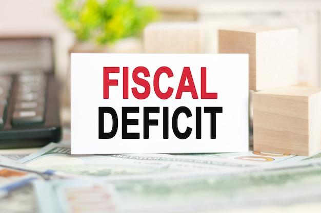 Слова фискальный дефицит написаны на белой бумажной карточке рядом с деревянными кубиками, банкнотами, черным калькулятором и зеленым растением позади.