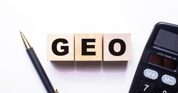 Geo라는 단어는 밝은 표면에 펜과 계산기 사이의 나무 큐브에 쓰여 있습니다.