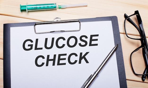 Надпись glucose check написана на белом листе бумаги рядом с очками в черной оправе, ручкой и шприцем. медицинская концепция