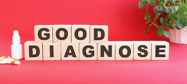 Good diagnose라는 단어는 의료용 약물과 함께 빨간색 배경에 나무 큐브로 이루어져 있습니다.